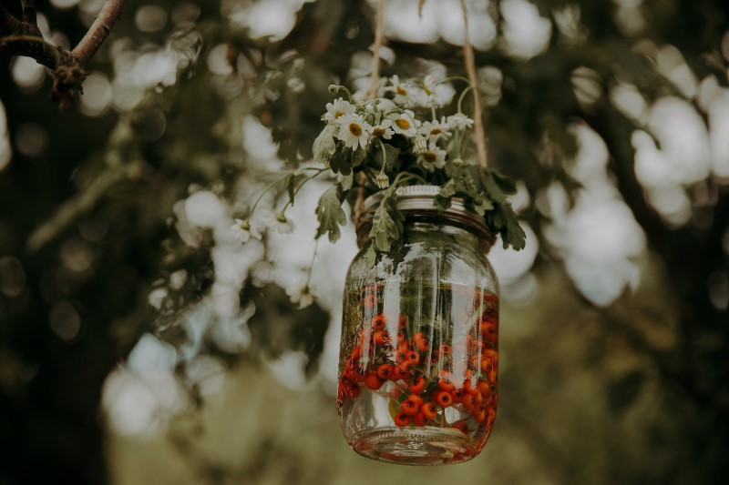Glass Jar with orange berries and white daisies hanging from tree at wedding ceremony