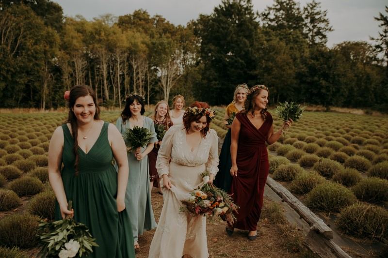 Bride and bridemaids walk through lavender field with hair by Brooklynn Seefried of Head Case Hair Studio on Vancouver Island