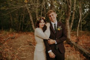 Newlyweds lean on each other in the forest by LumiPhoto