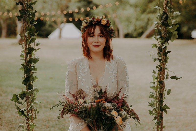 Charming Farm Wedding bride sitting on ivy swing with bouquet by LumiPhoto