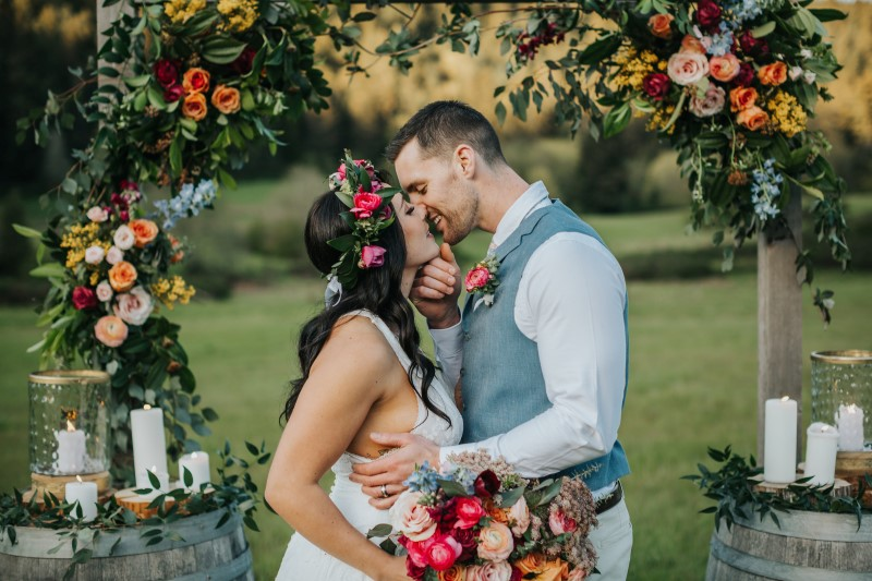 Newlyweds kiss at outdoor dance with cafe lights