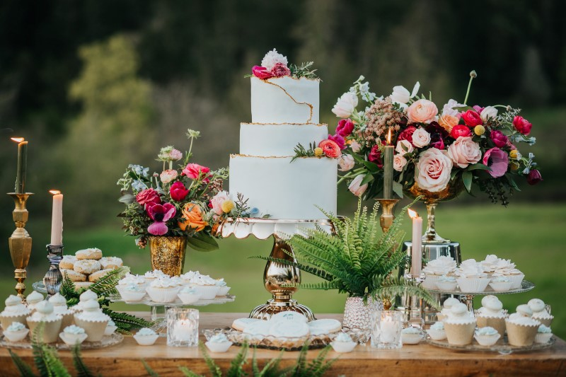 White wedding cake with pink, purple and white roses, peonies and anemones on dessert trolley
