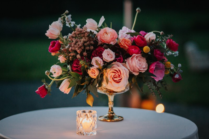 Incredible Wedding Reception Floral Arrangement in gold candlestick with roses anemones, peonies in pinks and purple tones by Lauren Riley