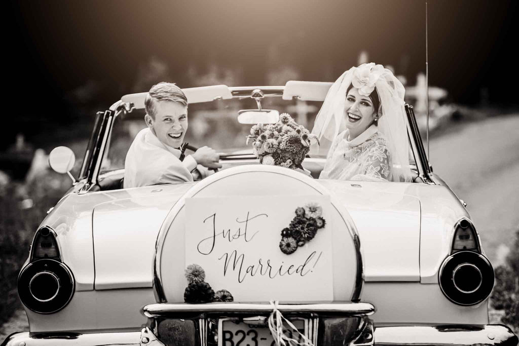 Retro newlyweds wave from vintage car with just married sign