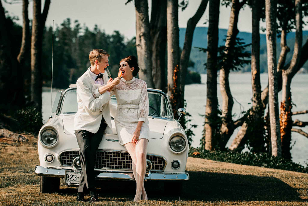 Twiggy Eyes + The Beehive retro couple eat popsicles against vintage car along the ocean
