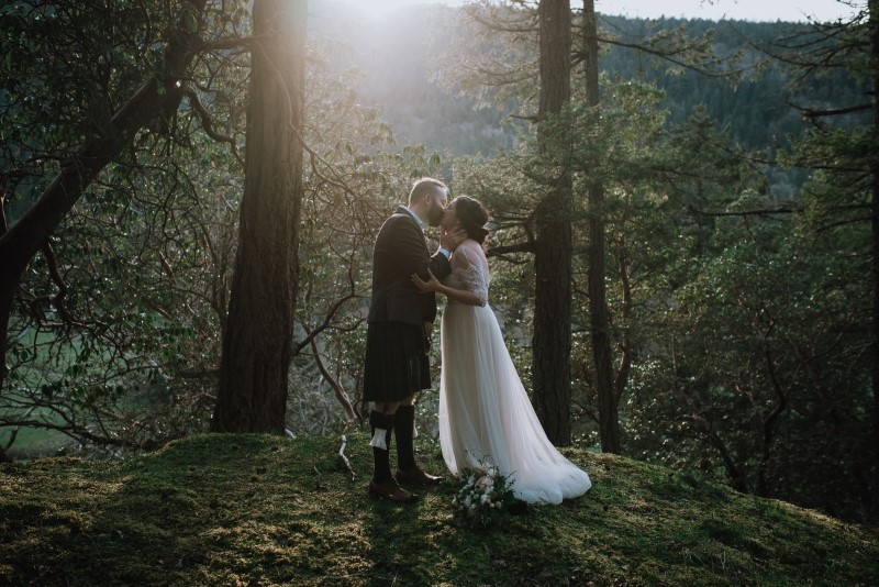 Newlyweds kiss in the forest with sunrise behind them by Three Sisters Photography