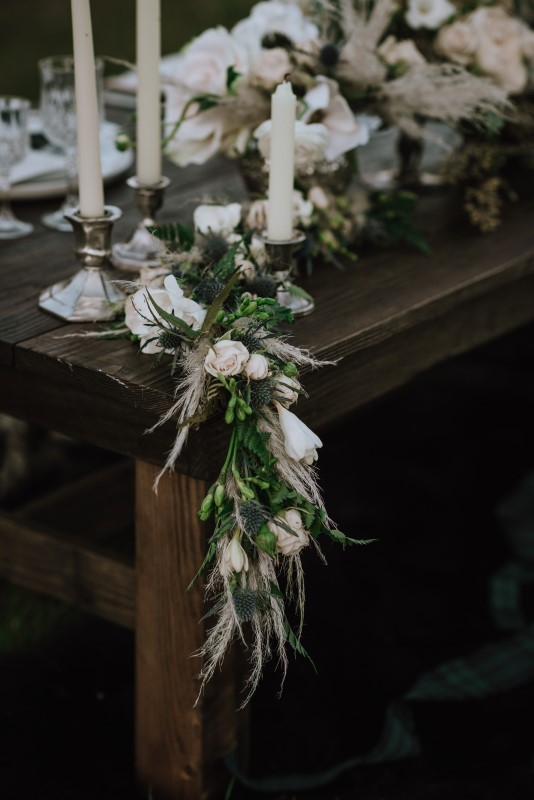 White rose garland on brown wood table by bespoke blossoms