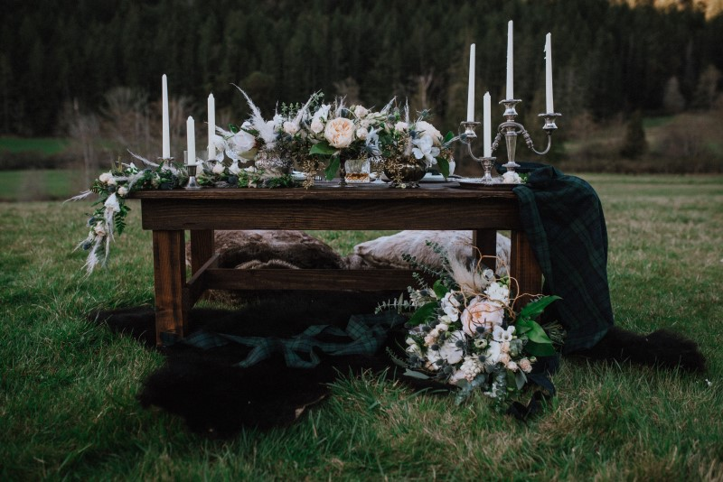 Low Sweetheart Wedding Table in Field on Vancouver Island covered in candles and white roses