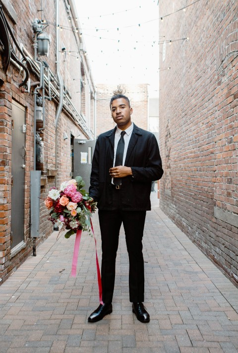Groom Holding Bouquet by En Vied Events in Victoria