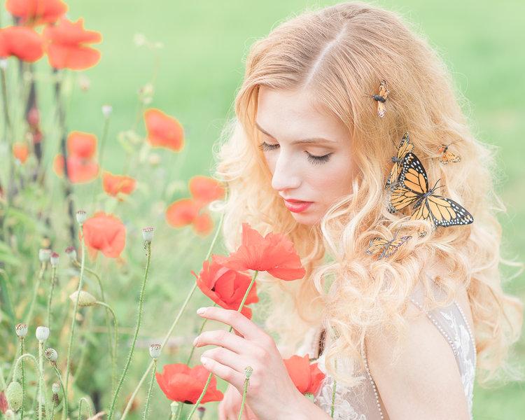 Bride smells orange poppies in LuxxNova wedding gown with butterflies in her hair