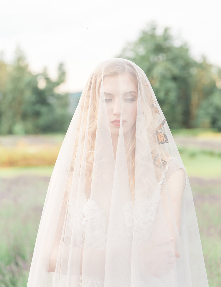Bride with long veil over her by Luxx Nova Vancouver