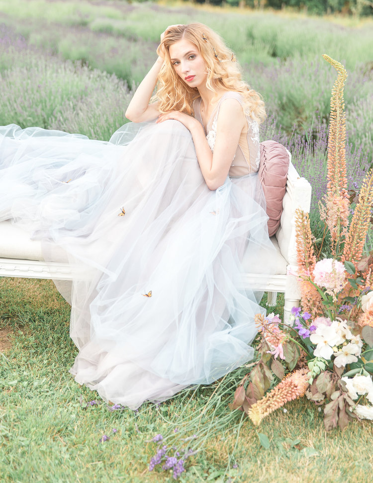 Bride Sits on Bench in LuxxNova gown surrounded by flowers in lavender field