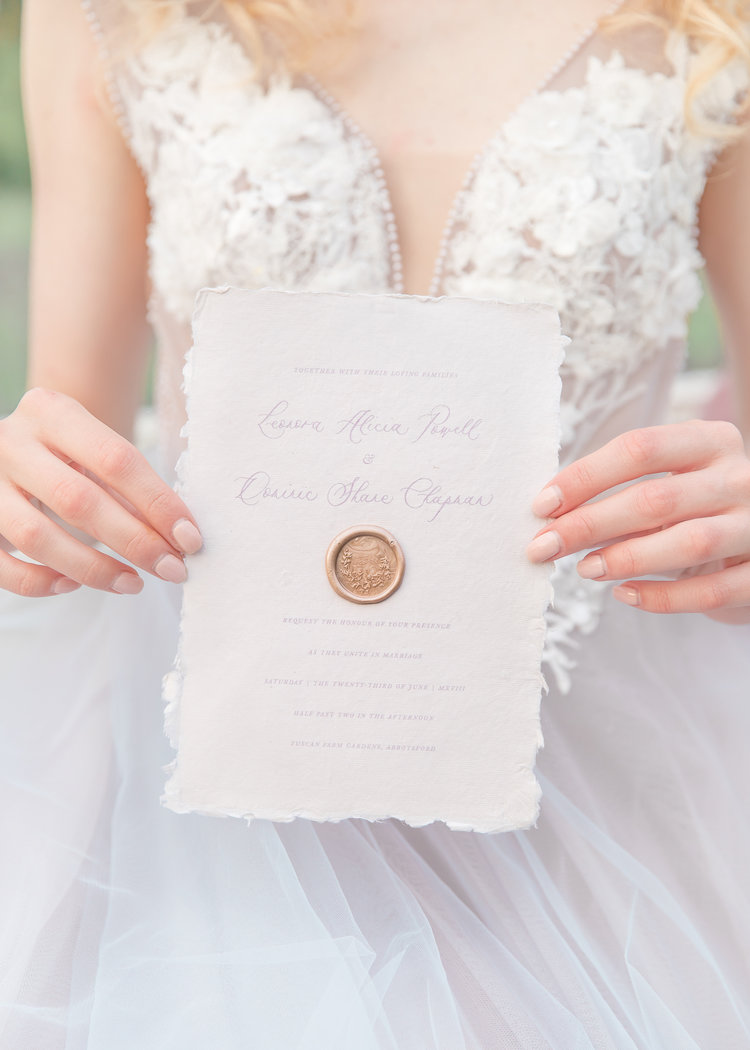 Bride holds embossed wedding paper suite by The Ayla View