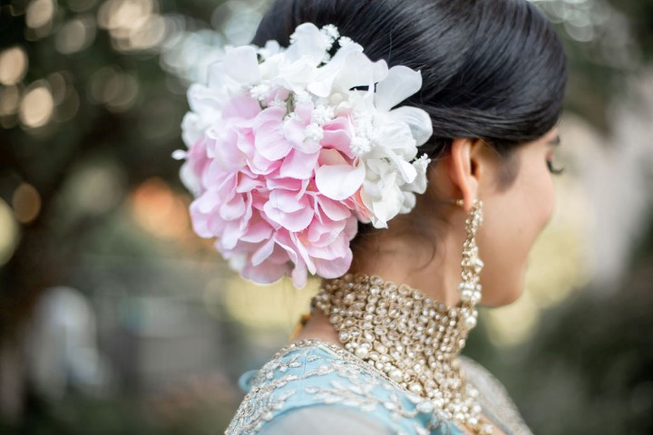 Bride wears pink and white dahlias in her hair along with diamond jewelry