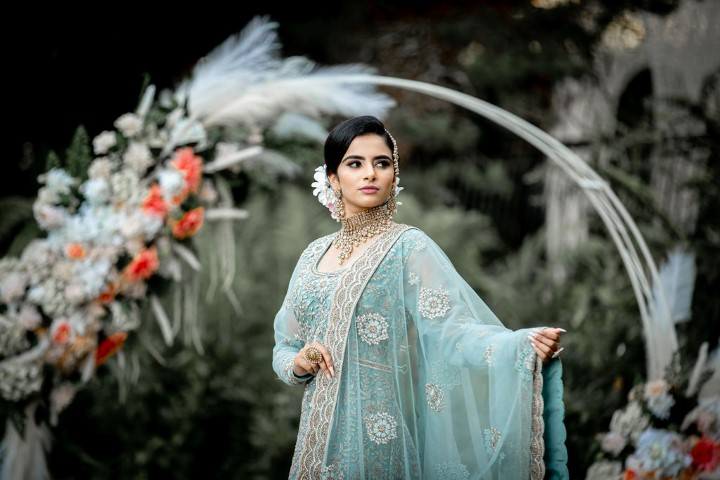 Indian Bride holds out her ice blue and white lace sari in front of wedding hoop