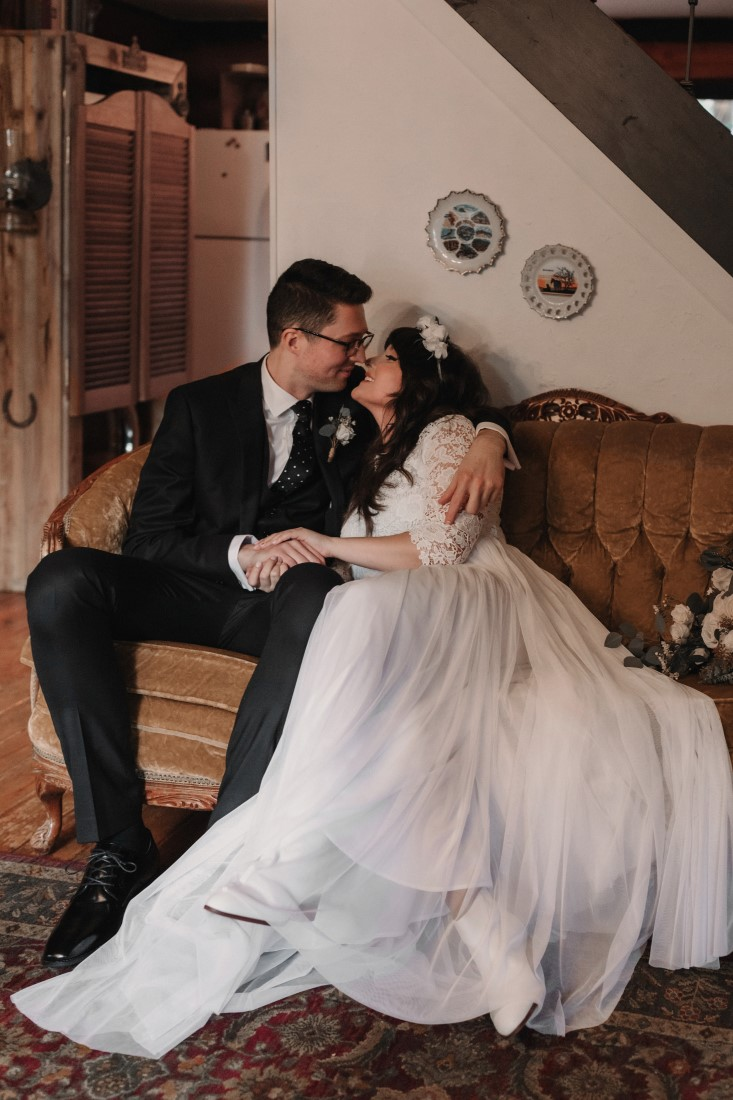 Newlyweds sit on wood bench with brides gown all around them
