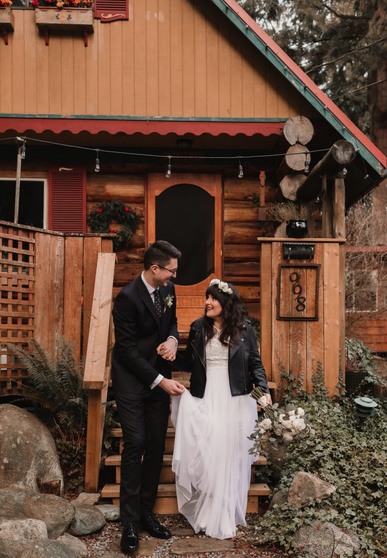Bride and groom sit on the stairs of a rustic cabin by Coastal Weddings and Events