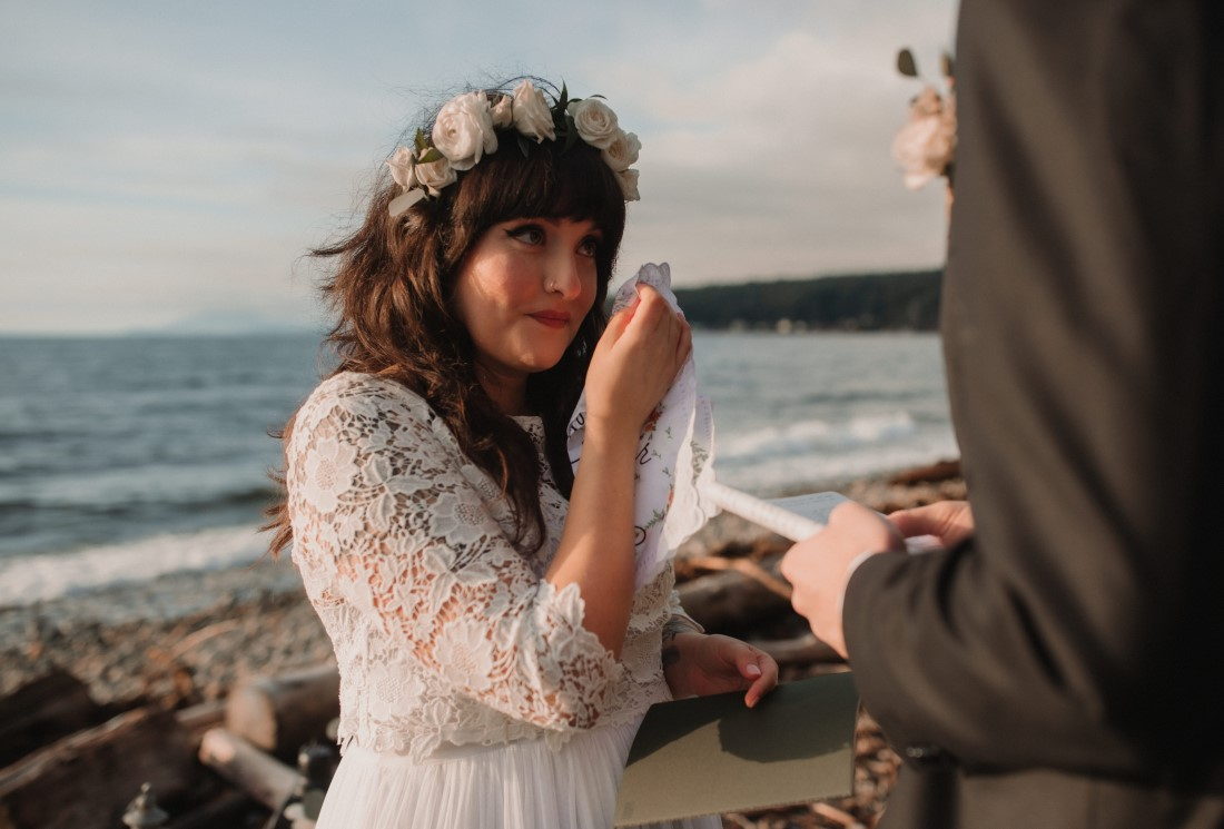 Bride wipes away tears as she exchanges vows at beach wedding ceremony