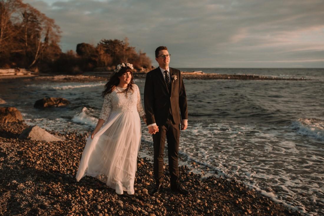 Newlyweds brace against the wind on the Sunshine Coast beach near Vancouver