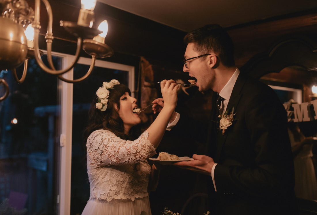 Bride and groom feed each other Sweet Athena cake
