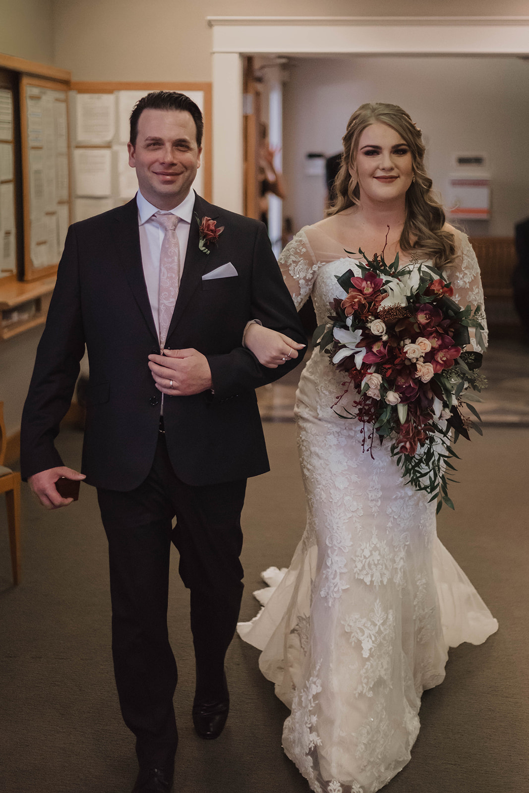 Father walks bride in form fitting lace gown