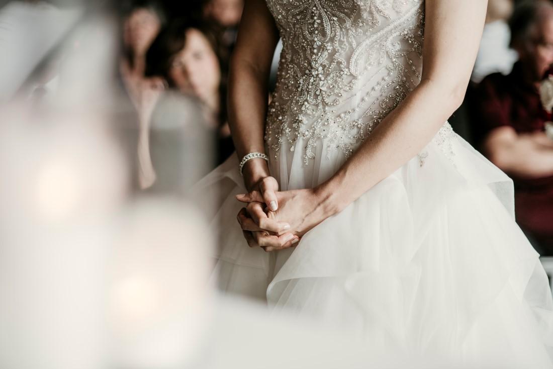 Bride holds her hands together in front of her dress during Black Rock ceremony