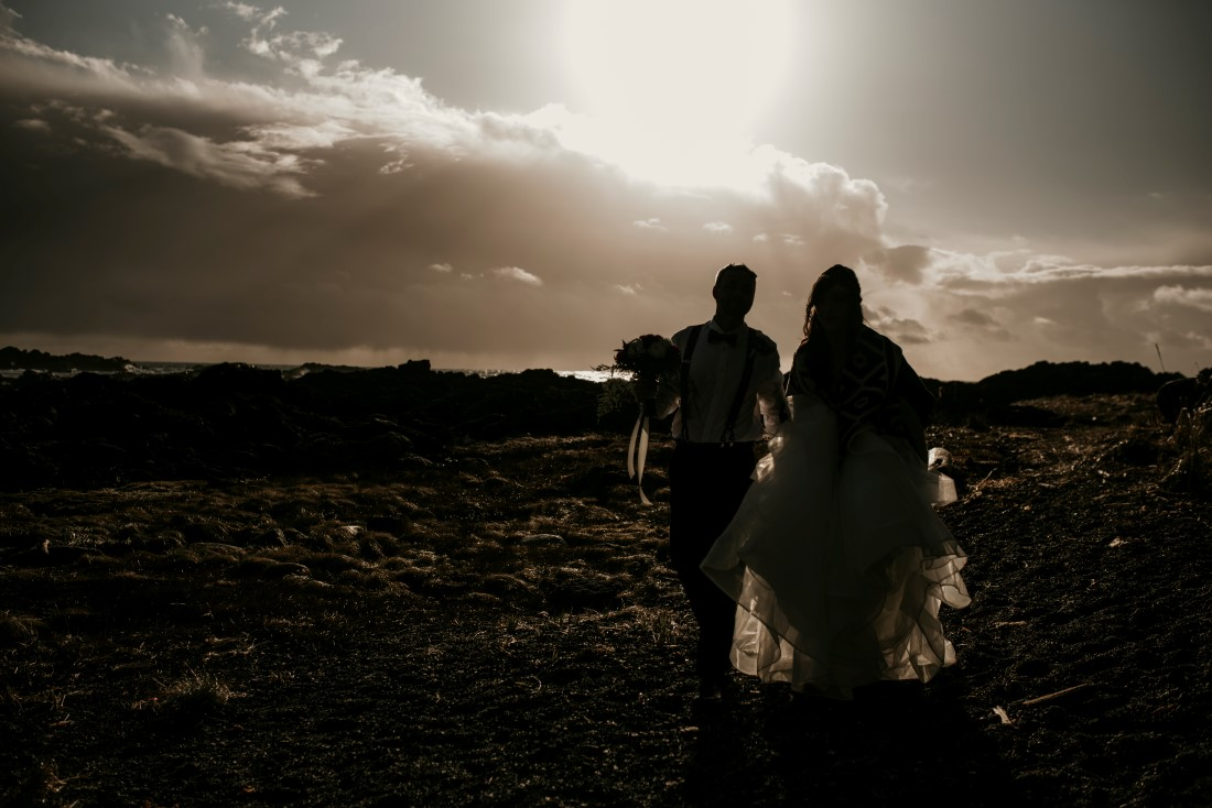 Newlyweds walk along the ocean during sunset by Jen McLeod Photography
