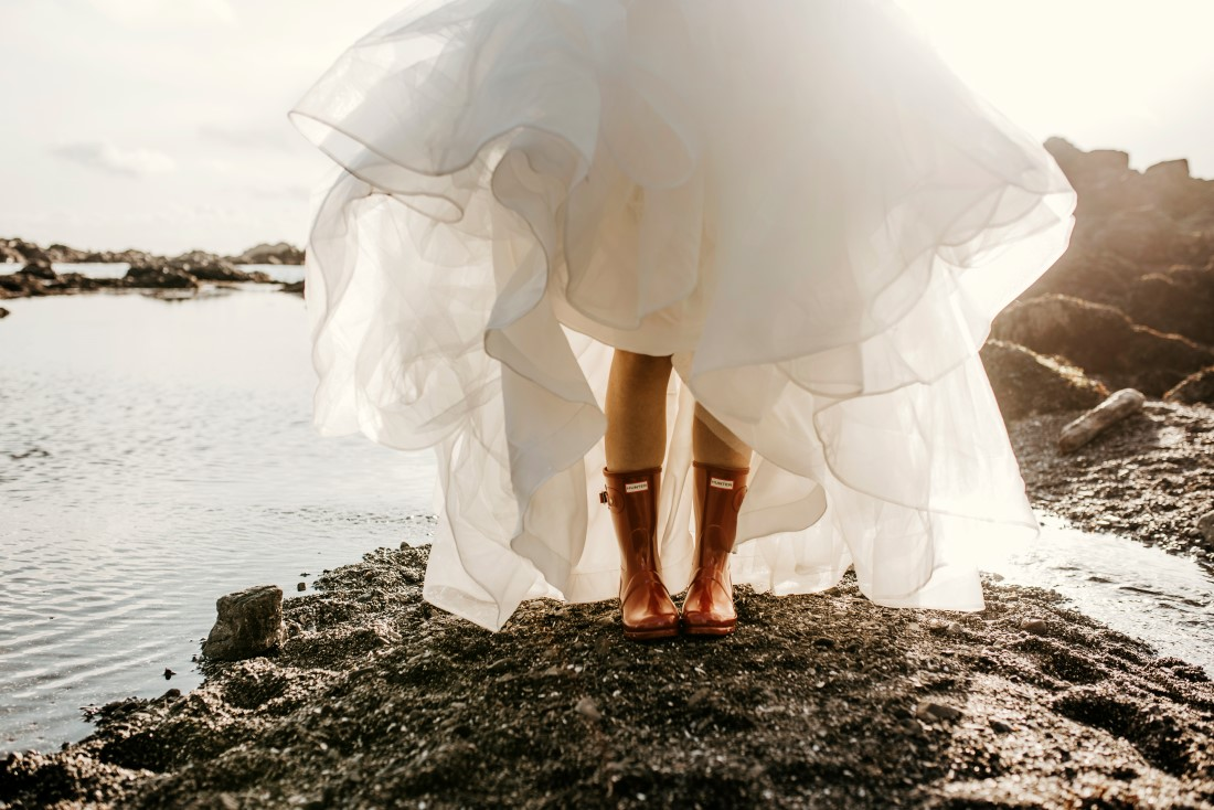 Brides shows off yellow rubber boots while standing along ocean in bridal gown by Shades of White