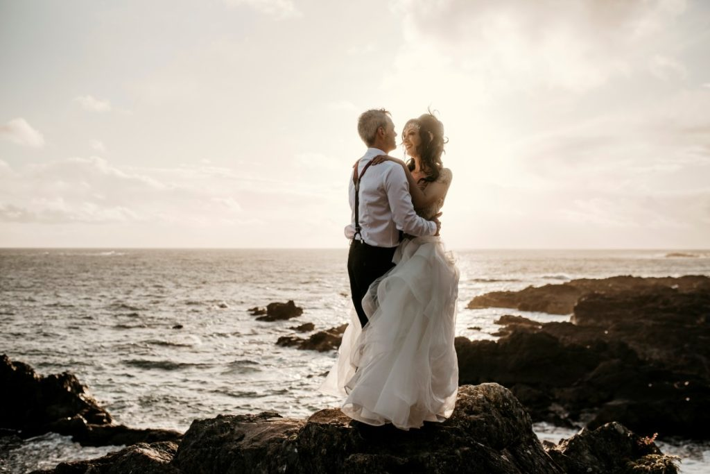 Bride and groom hold each other while looking out over the ocean on Vancouver Island