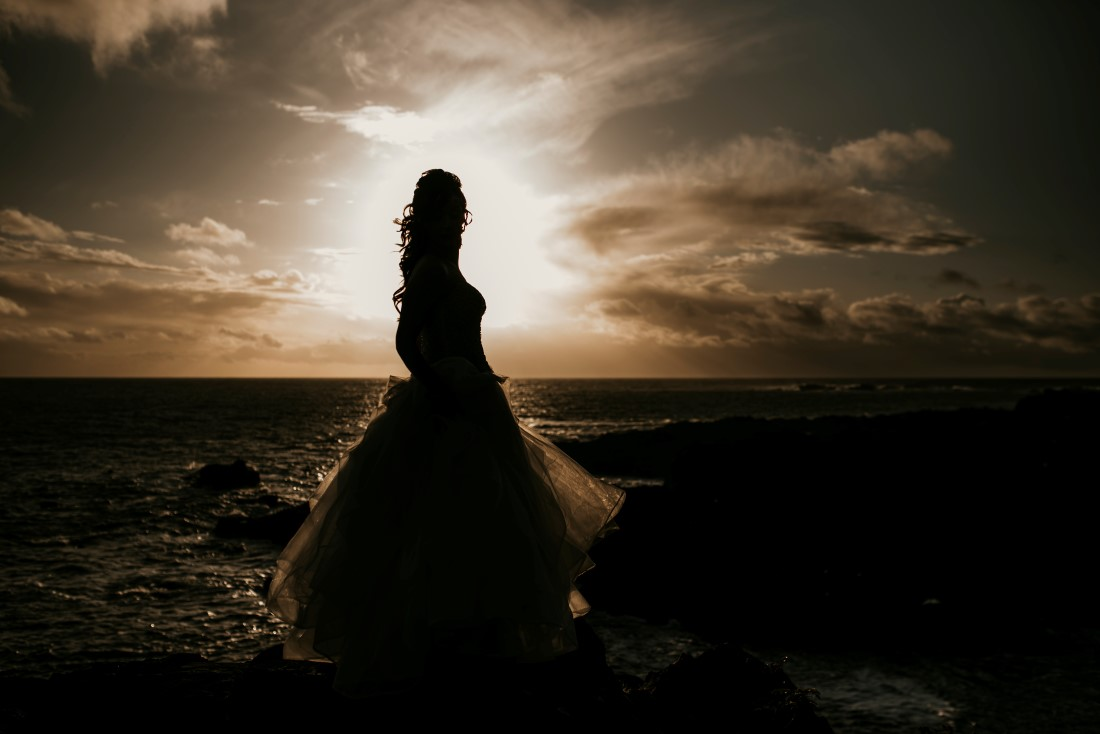 Bride standing beside the ocean is highlighted by the sunset in Tofino Vancouver Island