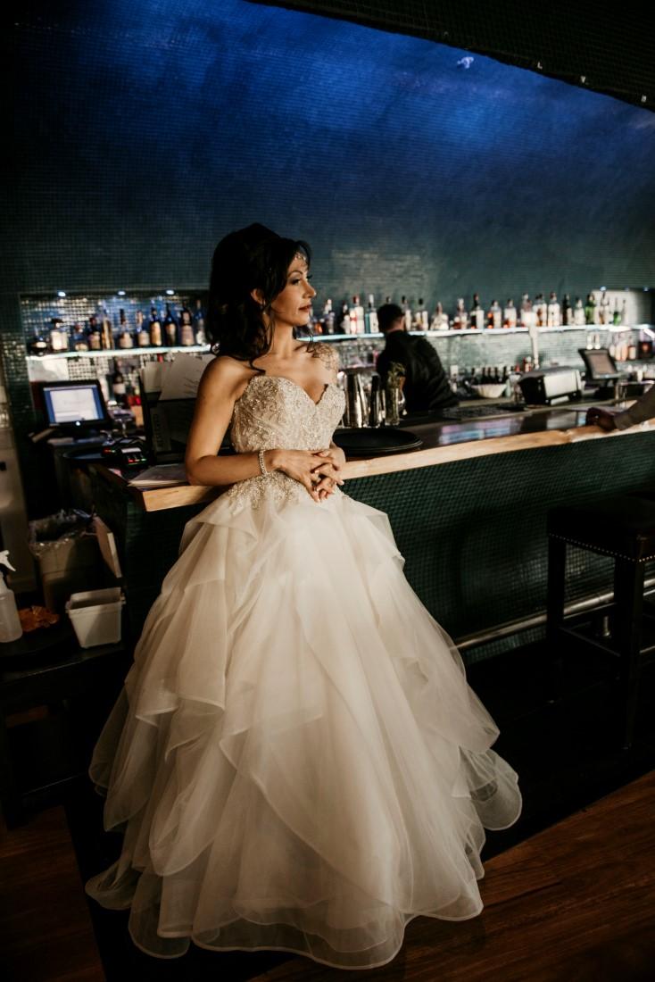 Bride leans against blue tile Big Beach Bar and Lounge at Black Rock Oceanfront Resort Vancouver Island