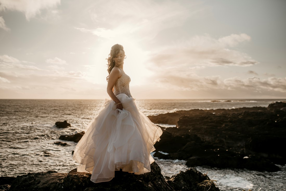 Bride stands on the black rock of Ucluelet holding her gown from Shades of White Vancouver Island