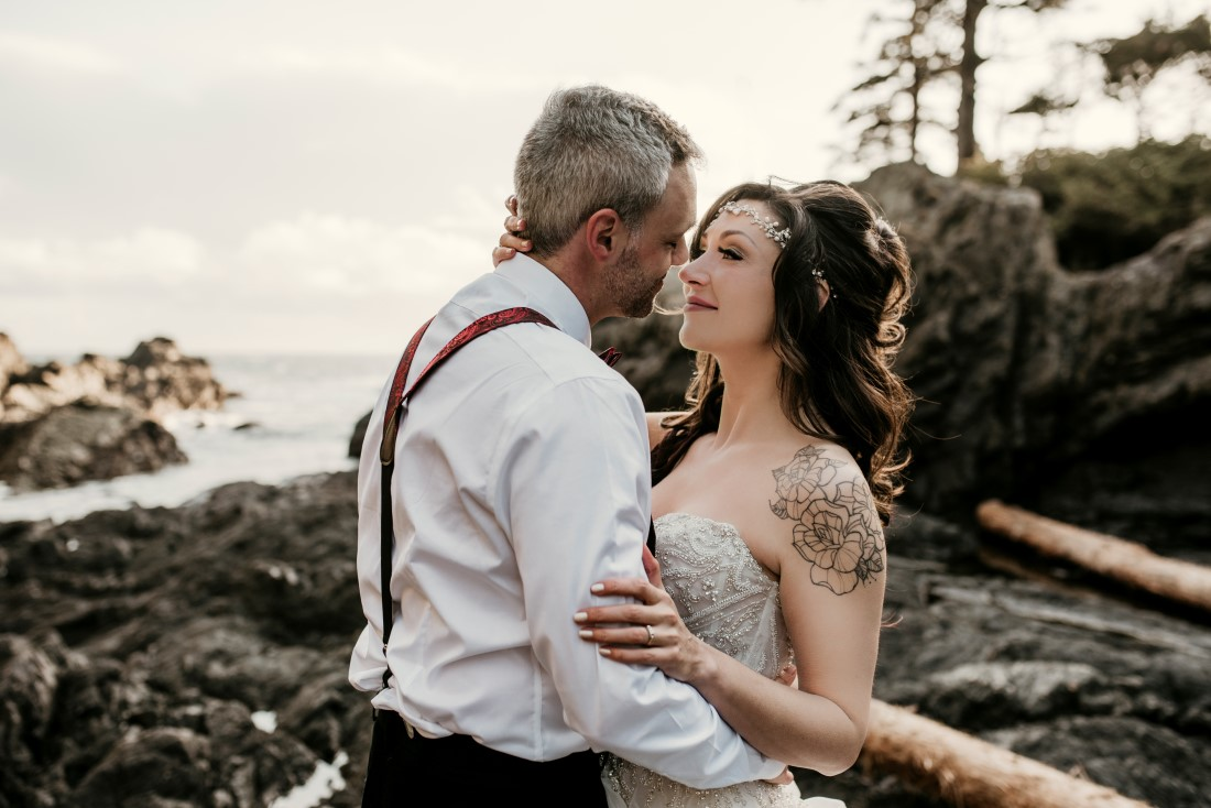 Bride with arm tattoo and groom wearing suspenders stand on beach surrounded by driftwood
