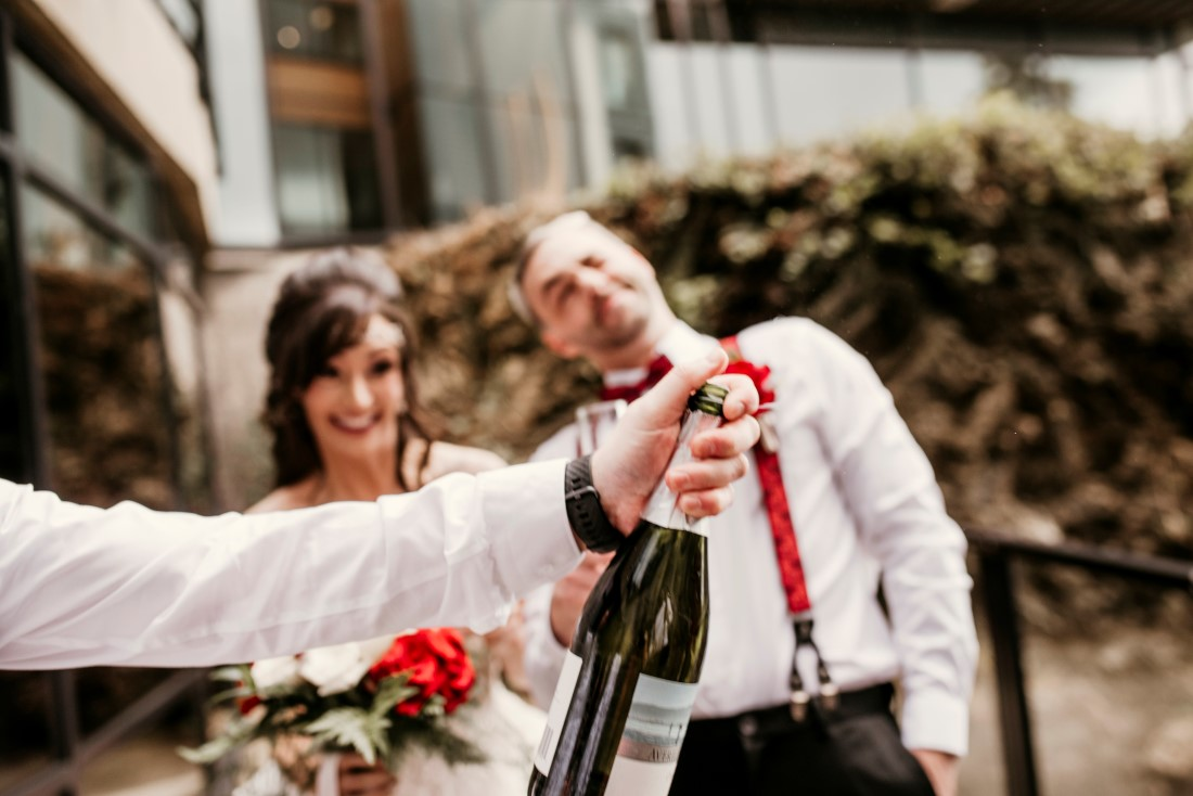 Newlyweds celebrate with champagne while holding rose bouquet by Crabapple Floral Tofino
