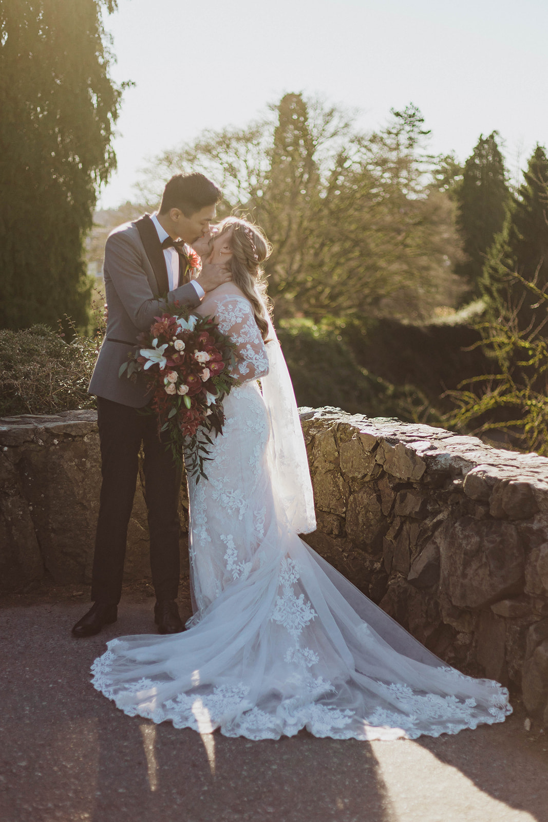 Newlyweds kiss in the sunset with bride wearing lace gown with train and veil by Blush Bridal Victoria