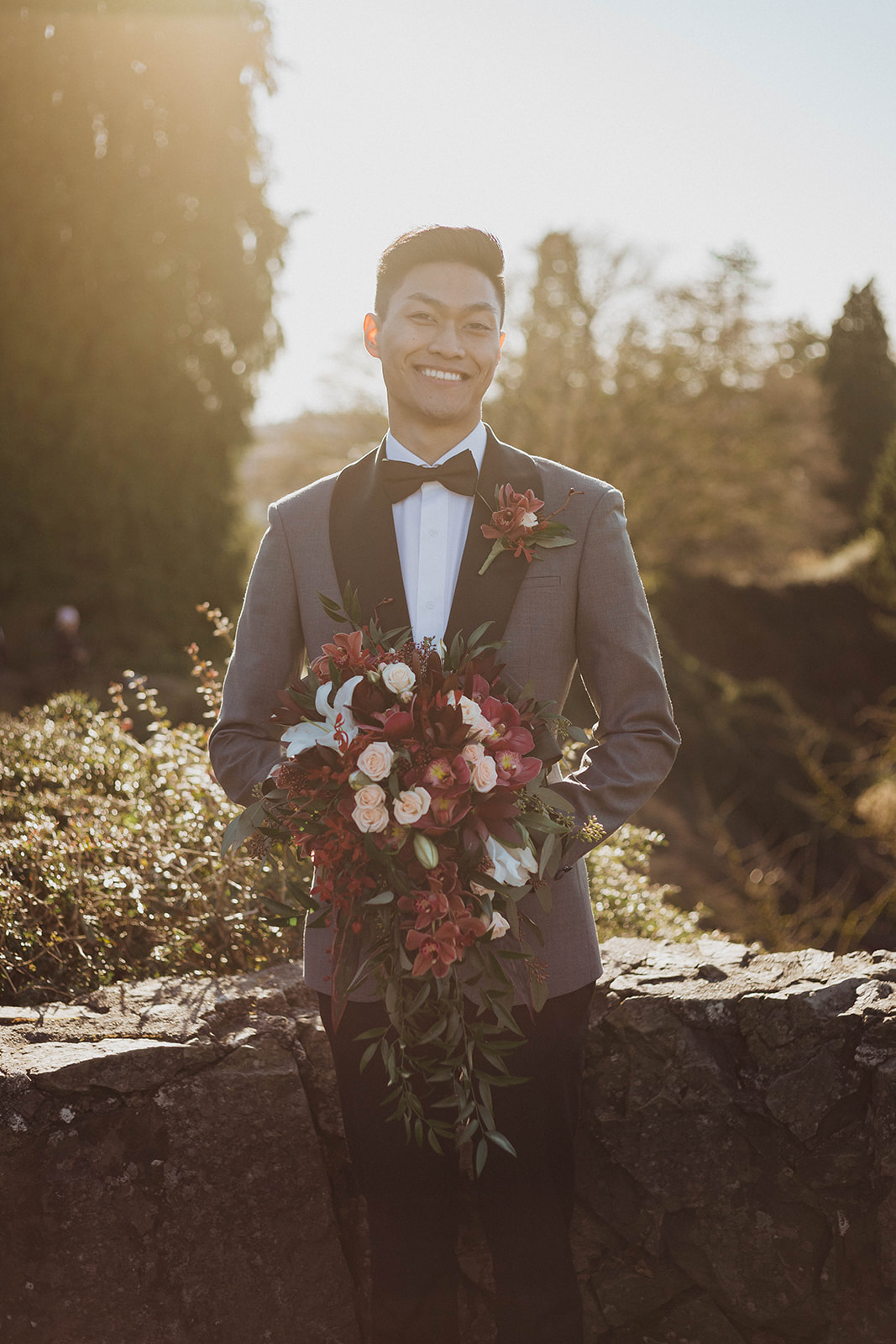 Sumesur groom in blue grey jacket with black lapels holding bridal bouquet by Niki Trading Vancouver