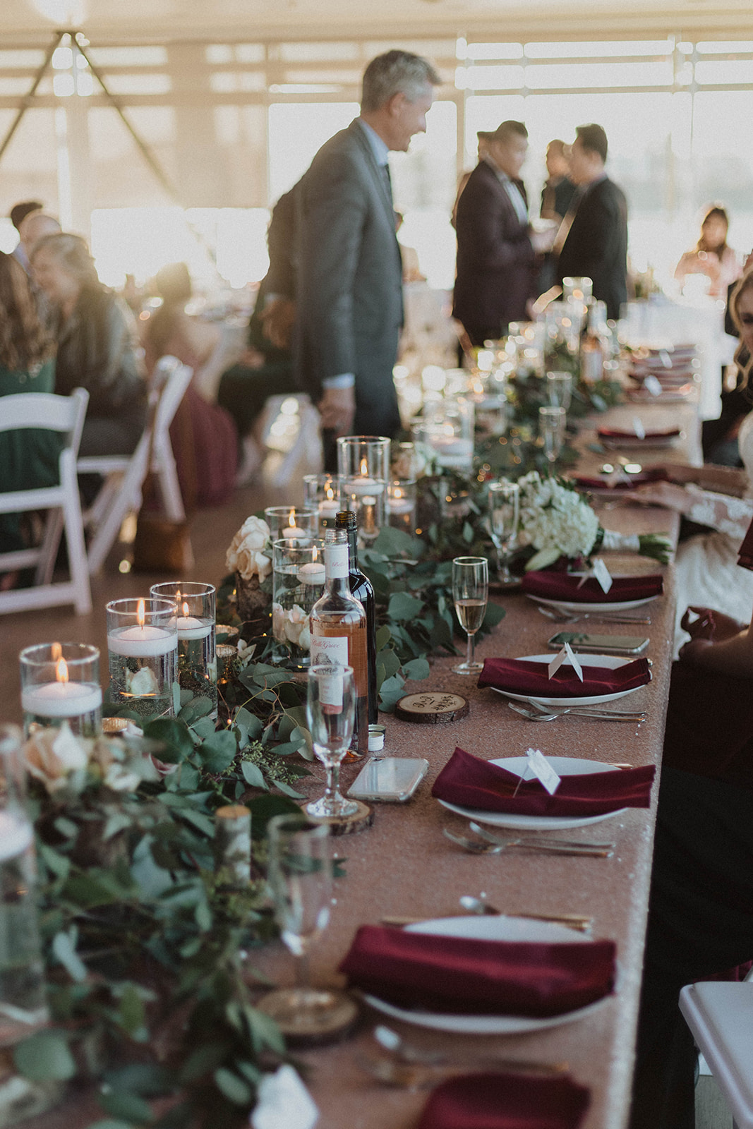 UBC Boathouse Wedding head table decor floating candles, eucalyptous and log rounds with blush pink roses