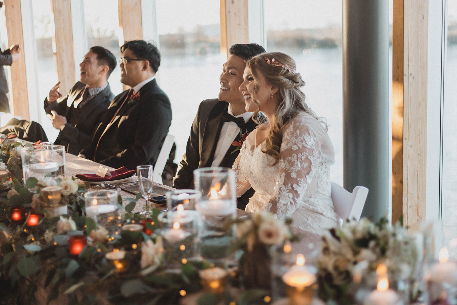 UBC Boathouse Couple sit at head table with Vancouver waterfront behind them by Kacie McColm