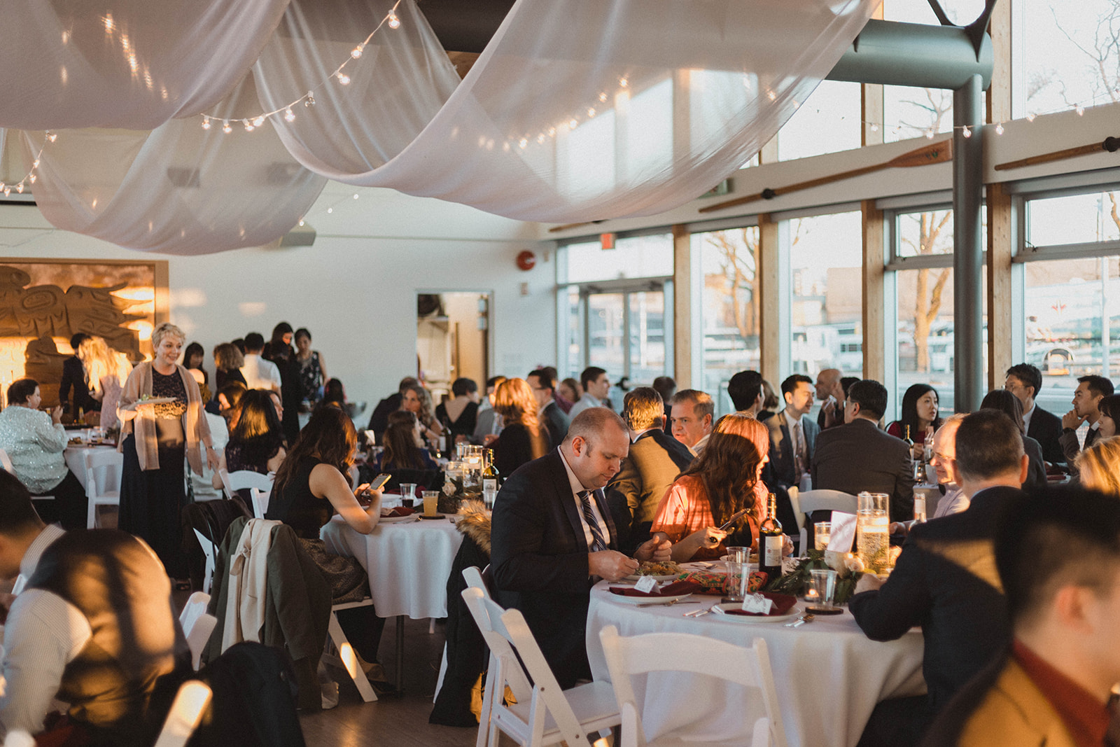 UBC Boathouse Wedding Reception guest sit below white fabric ceiling treatment by Proline International Trading Vancouver