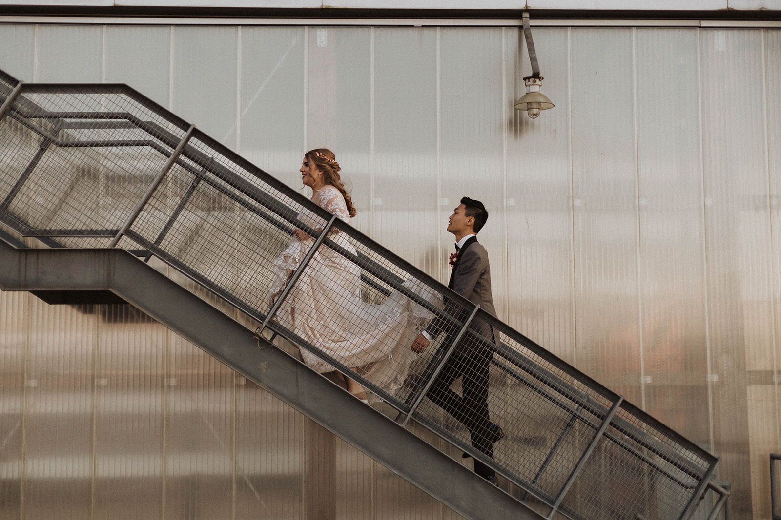 UBC Boathouse wedding couple walk up the metal staircase to reception in Vancouver