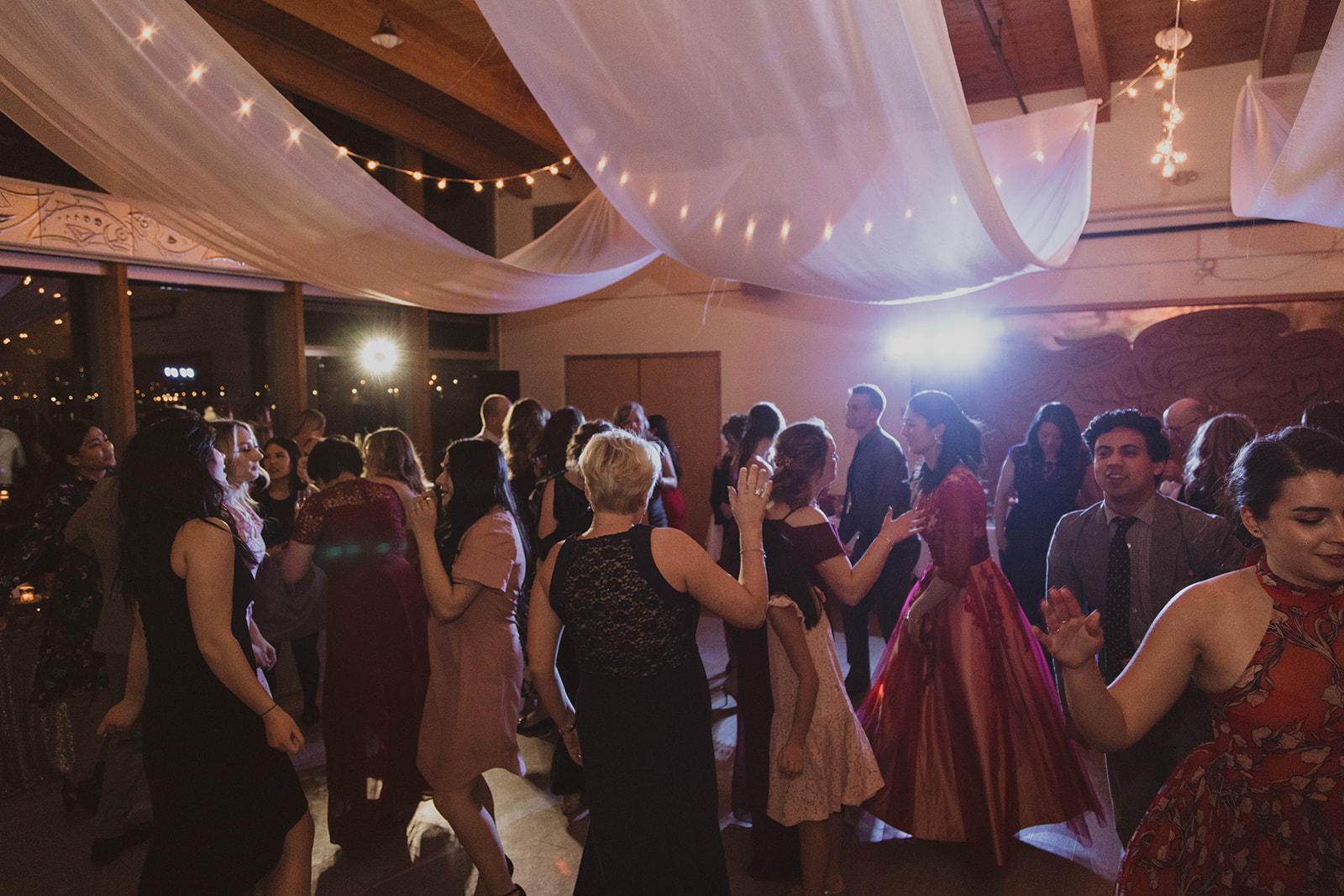 UBC Boathouse Wedding guests dance under white fabric ceiling treatment and industrial lights by Proline International Trading Vancouver
