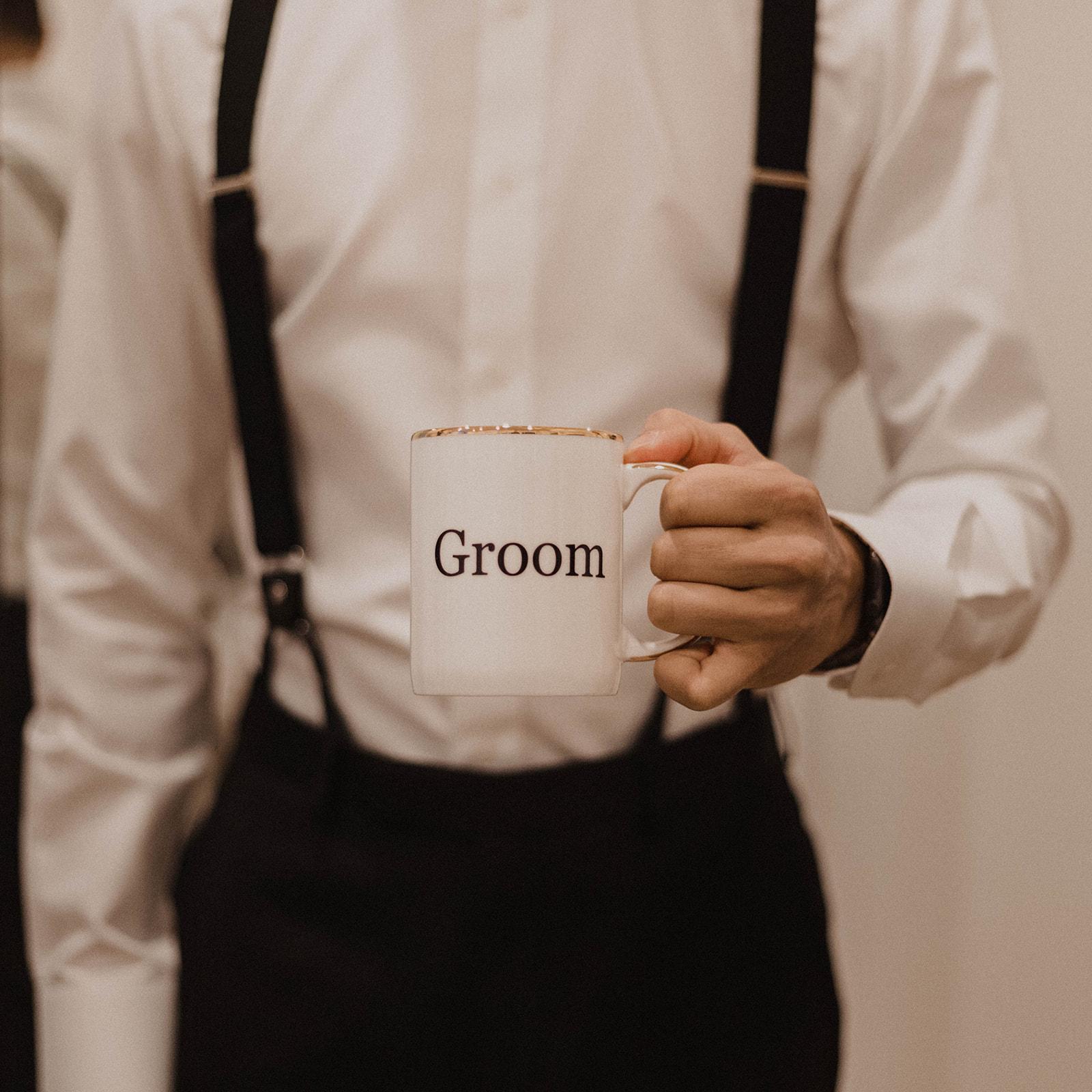 Groom in black suspenders by Surmesur holds groom mug