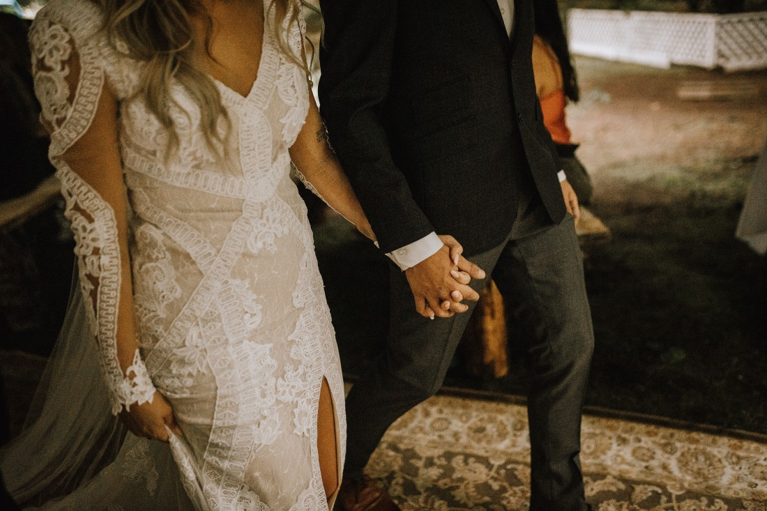 Bride and groom hold hands while walking through field at Farm Table Inn Lake Cowichan