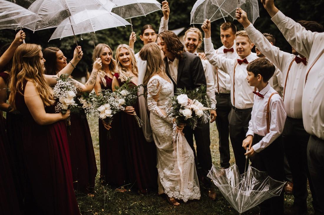 A Farm Table Wedding party laughs under umbrellas by Wild Oak Collective