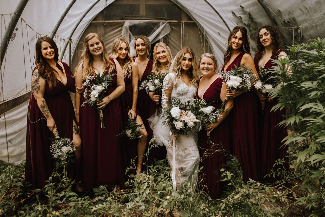 Bride and Bridesmaids in burgundy gowns smile and laugh in a field