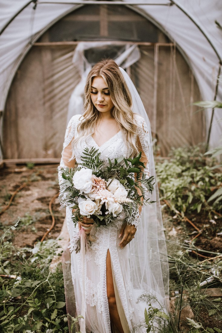 Bride holds bouquet of white flowers and greenery wearing Willowby and Watters by Shades of White