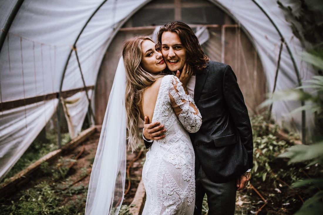 A Farm Table Wedding couple smile under tent on their wedding day