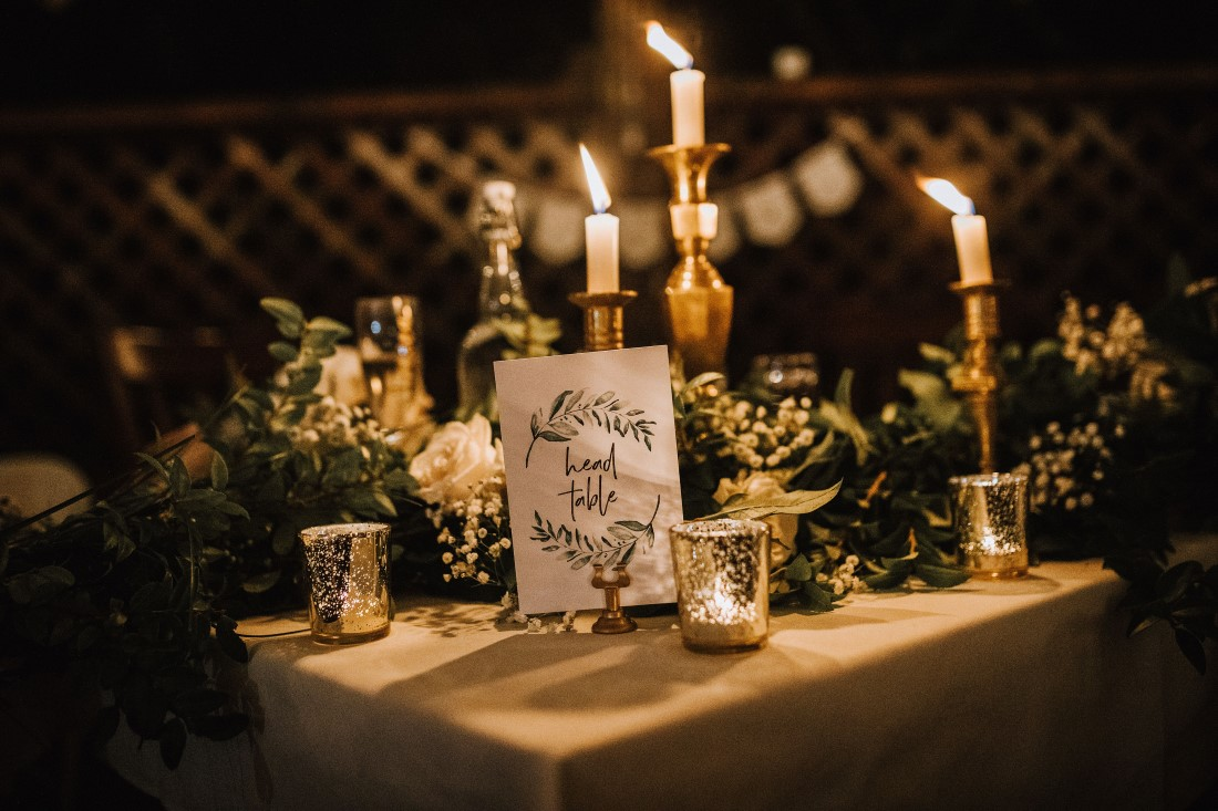 Tapered candles, greenery and sign on wedding guest table by Flourish Events Vancouver