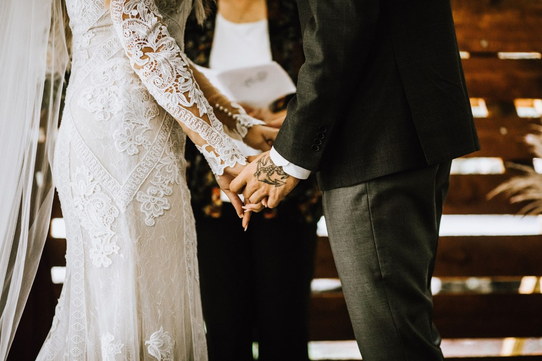 A Farm Table Wedding Couple hold hands during their vows by Flourish Events