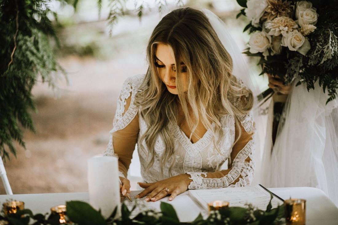 Bride signs register at farm wedding by Wild Oak Collective Vancouver Island
